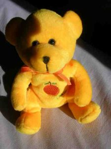 Yellow teddy with an apricot on its chest