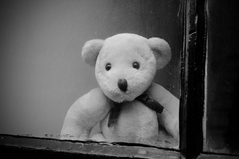 Sad looking teddy bear looking out from behind a window