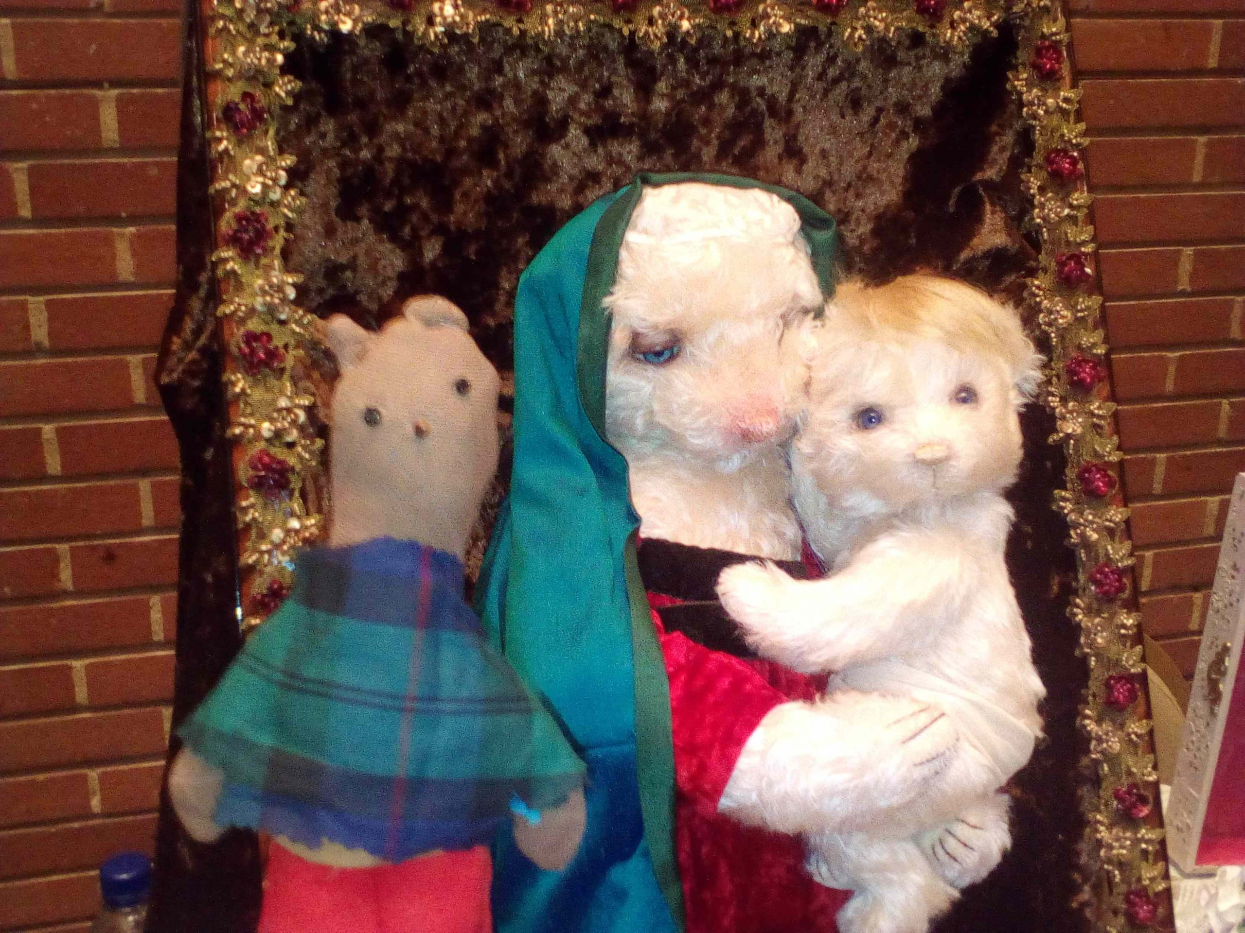 Mini-me version of Bearsac posing with Mary and baby Jesus teddy bears.