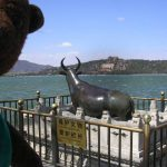 Bearsa beside brass bull beside lake