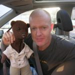 Jake Wood holding Bearsac in car window.