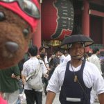 Bearsac in foreground of man wearing unusual hat