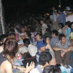 People sitting on ground waiting for fireworks.