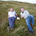 Clive Francis and Neil Capel sitting on grass with Bearsac between them