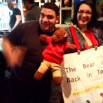 Bearsac and Debra with a man (Debra with poster saying 'The bear is back in town'.