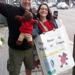 Man with Bearsac and Debra. Debra wearing home-made poster saying The bear is back in town. with her book cover and Bearsac underneath.