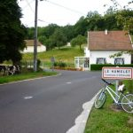 Bearsac on bicycle prompt up against place sign for Offanville