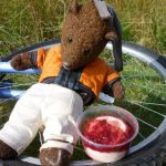 Bearsac sitting a bicycle wheel-cum-table with food.