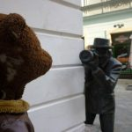 Paparazzi statue peering around corner with camera stalking Bearsac
