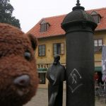 Bearsac beside the statue of writer August Senoa