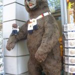 Bearsac sitting on arm of likely 8 foot tall toy bear
