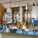 Bearsac at Bogor railway station with people sitting with the feet on the nearest track.