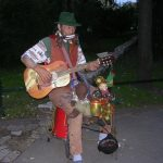 Bearsac sitting of the knee of a one-man-band busker with a clown puppet