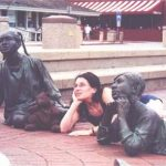 Debra and Bearsac sitting with brass children at foot of the Alex Haley monument